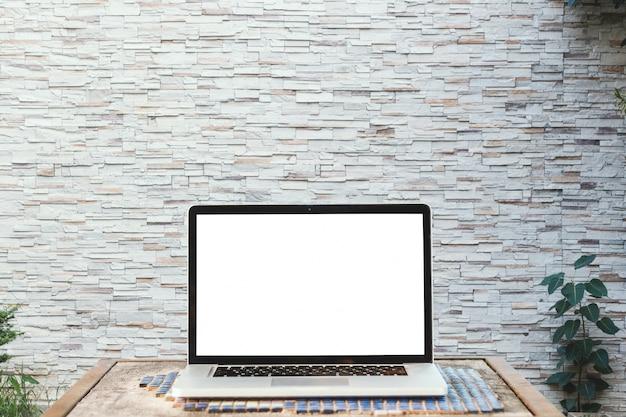 壁を持つ木製のテーブルの上の空白の白い画面を持つノートパソコンのモックアップ画像