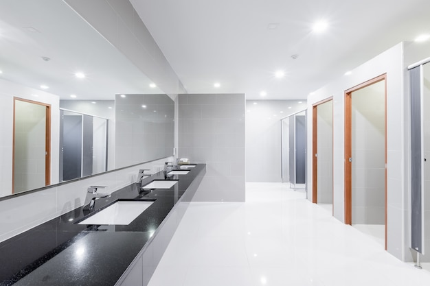 並ぶ流しの洗面台の蛇口付きのバスルームのパブリックインテリア