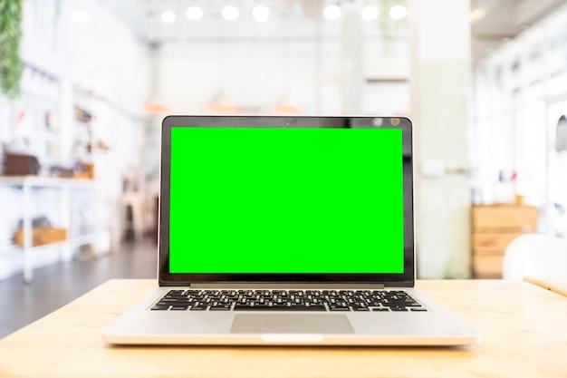 コーヒーショップでの木製のテーブルに空白の緑色の画面とラップトップのモックアップ画像。