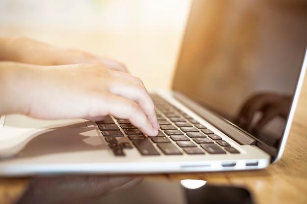コーヒーショップでノートパソコンやスマートフォンを扱うビジネス女性のクローズアップ