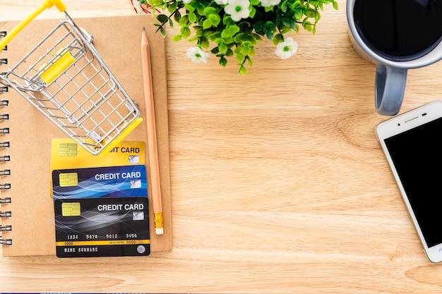 クレジットカード、ノートブック、植木鉢、スマートフォン、木製の背景、オンラインバンキングトップビューオフィステーブルにショッピングカートとコーヒーカップ。
