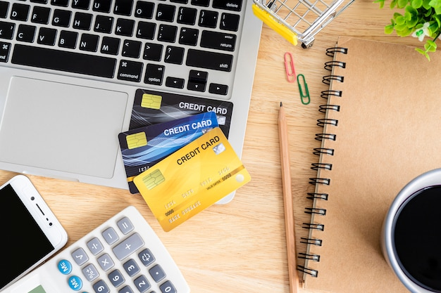 ノートパソコン、ノートブック、植木鉢、スマートフォン、木製の背景、オンラインバンキングトップビューオフィステーブルに電卓でショッピングカートにクレジットカード。