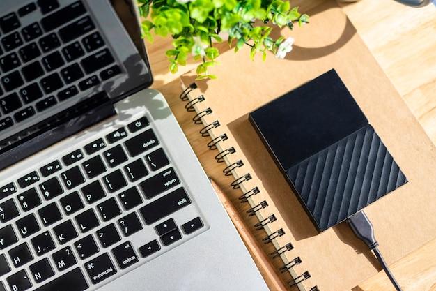 木製の背景、トップビューオフィステーブルに鉛筆とフラワーポットツリーとノートパソコンのキーボードとノートブックの外付けハードディスク。