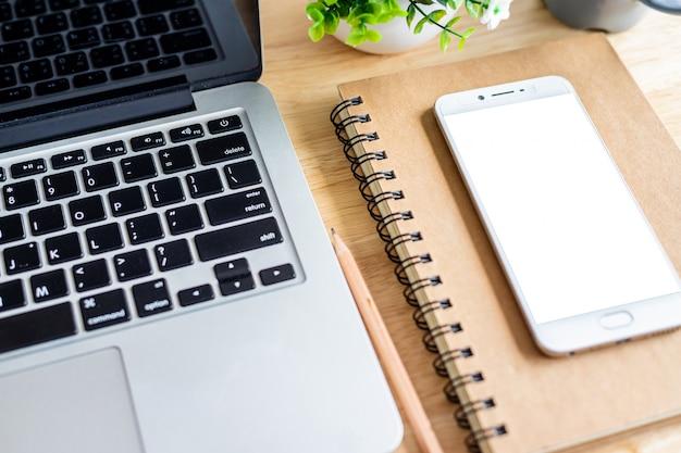 ノートブックとデスクトップ上のラップトップを持つスマートフォン