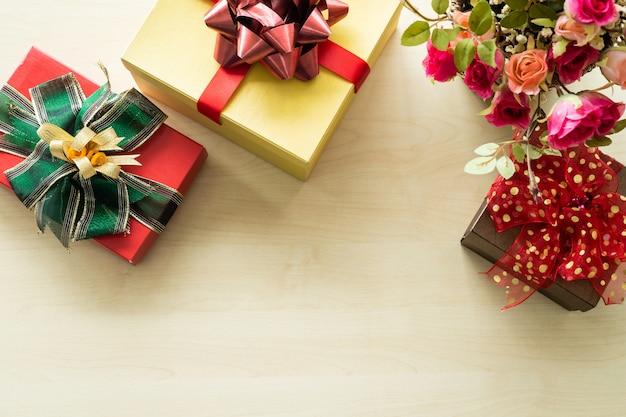 クリスマスバラの花瓶とトップビューの木製インテリアの多くの贈り物。クリスマスと新年の装飾。
