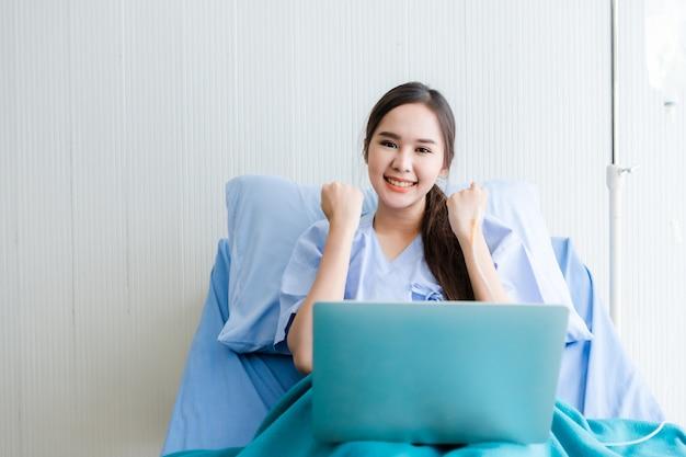 Азиатский молодой женский пациент выразил уверенность подбодрить на кровати и портативный компьютер в комнате больницы