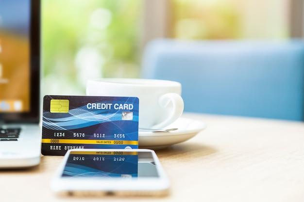 木製のテーブルにラップトップコンピューター、スマートフォン、コーヒーカップのクレジットカード