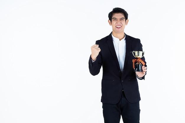 チャンピオンカップを保持しているハンサムな若いアジア系のビジネスマンを叫んで成功感勝者