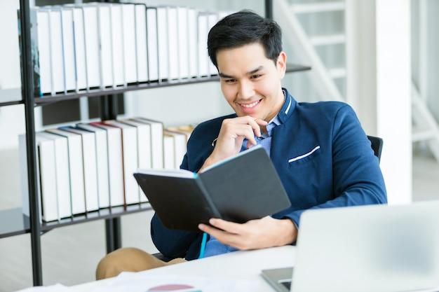 幸せな気分で働くアジアの青年実業家の陽気な記録されたメモを読む