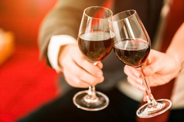 赤ワインのグラスを保持しているカップル