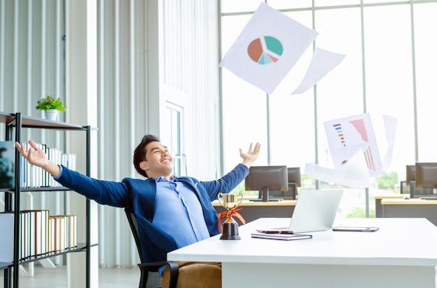 Счастливый успех азиатского молодого бизнесмена за подбросил бизнес-план в документ бумаги в воздух