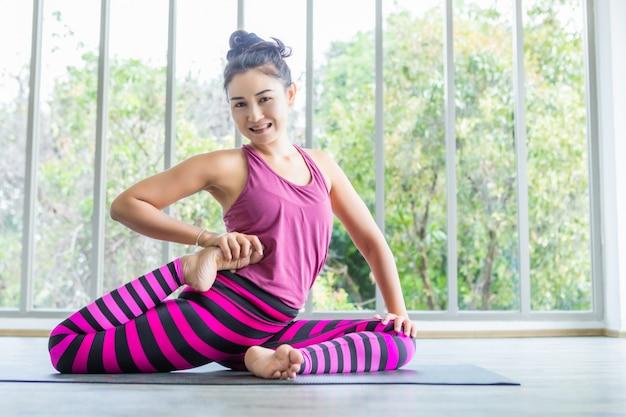 ピンクの服を着てヨガトレーニングを練習してアジアの女性のトレーニングと瞑想ウェルネスライフスタイルとジム、コピースペースで健康フィットネスの概念を練習