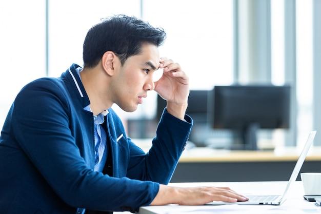 強調した実業家は、ラップトップコンピューターで作業し、事務室でのビジネス上の損失の後、頭痛を抱えています。