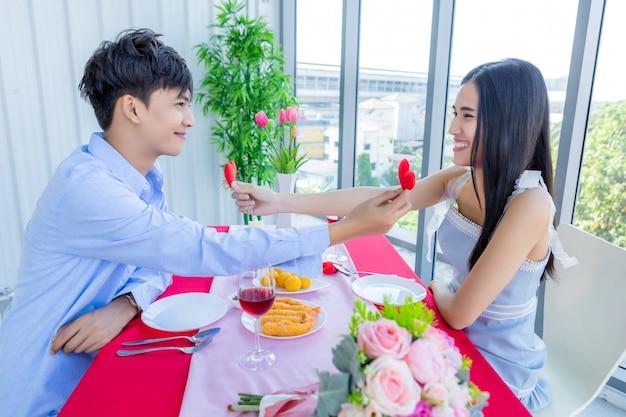 バレンタインのコンセプト、アジアの若い幸せな甘いカップルが小さな赤いハート型の枕を保持している愛のショーでレストランで昼食後