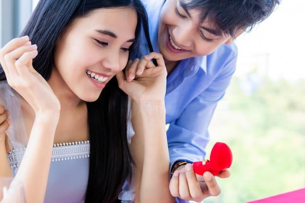 バレンタインの日とアジアの若い幸せな甘いカップルコンセプト、アジアレストランで昼食後女性への結婚の提案を行う婚約指輪を持つ男
