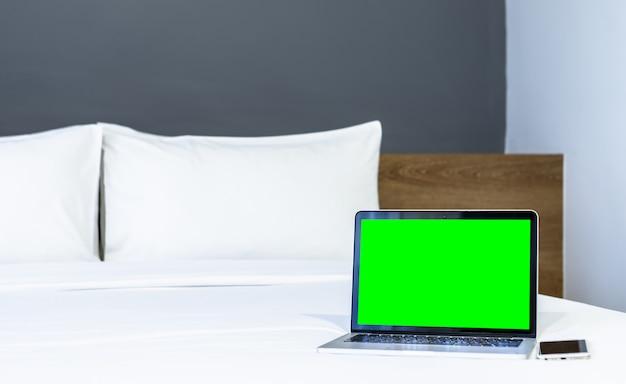 ホテルの寝室のインテリア、仕事、休日の概念の旅行とレジャーでビジネスの白いベッド装飾にスマートフォンで空白の画面を持つラップトップコンピューター。
