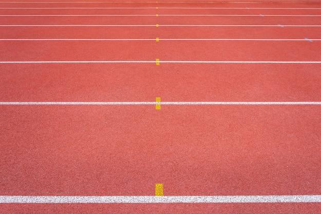 スタジアムの白い線と競馬場の赤いゴムの競馬場の質感