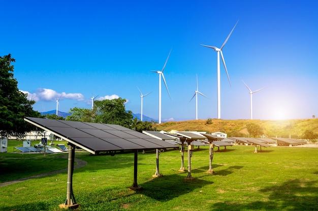 Панели солнечных батарей с ветряными турбинами против горизонта горы против голубого неба с облаками