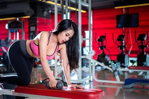 フィットネスアジア女性のジムの表現でダンベルスポーツトレーニング演習