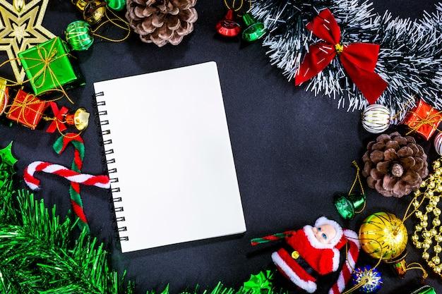 空のノートブックと黒い紙の背景に鉛筆でクリスマスのお祝い飾り