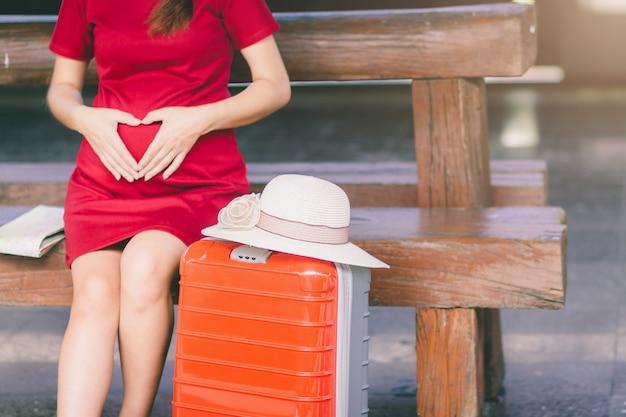 アジアの女性の妊娠中の赤いドレス