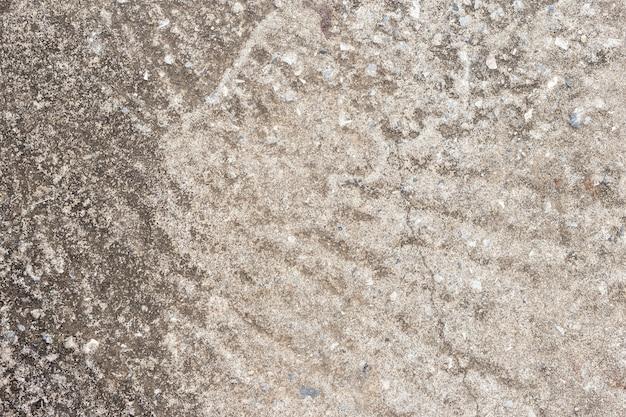 Абстрактная старая пакостная темная предпосылка стены цемента на земной текстуре.