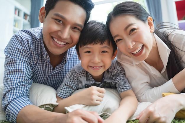 Счастливая азиатская семья тратя время совместно на софе в живущей комнате.