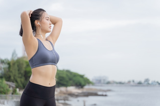 ビーチの海辺で実行されているトレーニングの後休んで若いアジア女性ランナー。