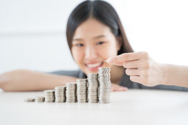 Молодая азиатская женщина делая стопку монет