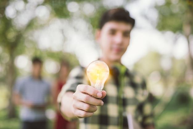 照明された球根を保持している男の十代の学生。