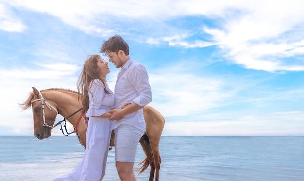海のビーチで馬とロマンチックな愛するカップル