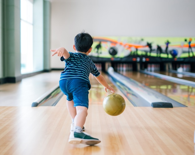 Вид сзади ребенок бросает мяч для боулинга