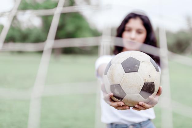 サッカーとぼんやりとした美しい十代の少女サッカーボールの背景を持って