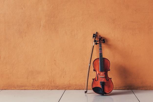 オレンジ色のセメントの壁に古代の古典的なバイオリンを置く