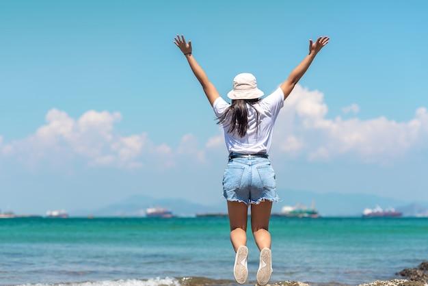 美しい少女の裏側は腕を伸ばして青い空の真っ只中にビーチでジャンプします。