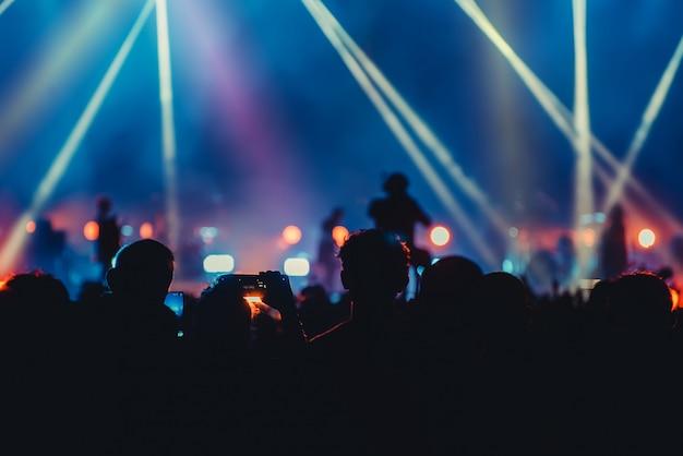 シルエット画像とステージ上のエンターテイメントコンサートのカラフルな照明のデフォーカス
