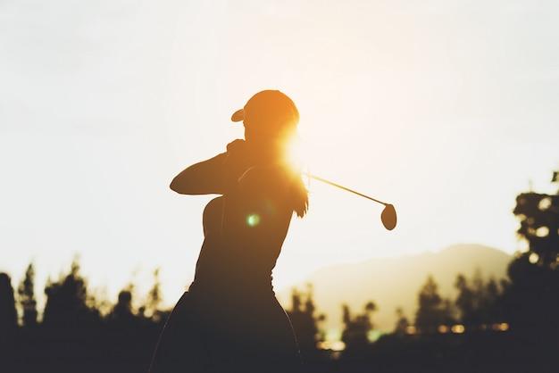 若い女性のゴルフプレーヤーのシルエットが抜本的なヒットし、ゴルフスイングを行うゴルフコースを維持、彼女はリラックス時間、ビンテージトーンの運動を行う