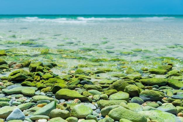タイアジアのスリチャンビーチの楽園。緑の石の素晴らしいビーチ。リラックスのための熱帯のビーチ。海岸の波。青い海のソフトウェーブ、セレクティブフォーカスをお楽しみください