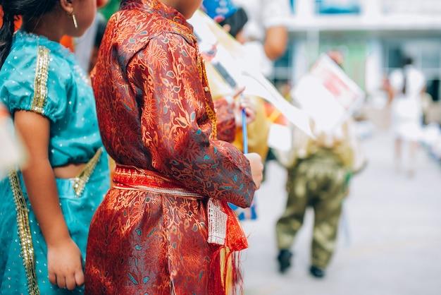 Национальное платье в день асеан. студенты держат в руках флаг ассоциации государств юго-восточной азии.