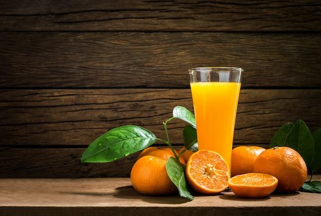 ビンテージの木のテーブルの新鮮なオレンジジュースの静物ガラス