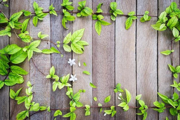 あなたのテキストを配置または春のコンセプトに文言のための木製の背景に葉のフレーム