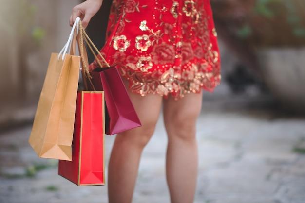 ショッピングのための買い物袋を保持しているチャイナドレスの伝統的な赤いドレスでアジアの中国人女性