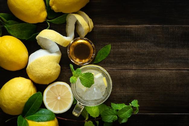 夏の木製テーブルのリフレッシュメントのレモネードソフトドリンクレモンジュースの上から見るガラス