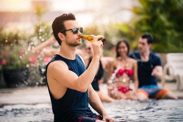ビール瓶を持ってプールパーティーを楽しむハンサムな男