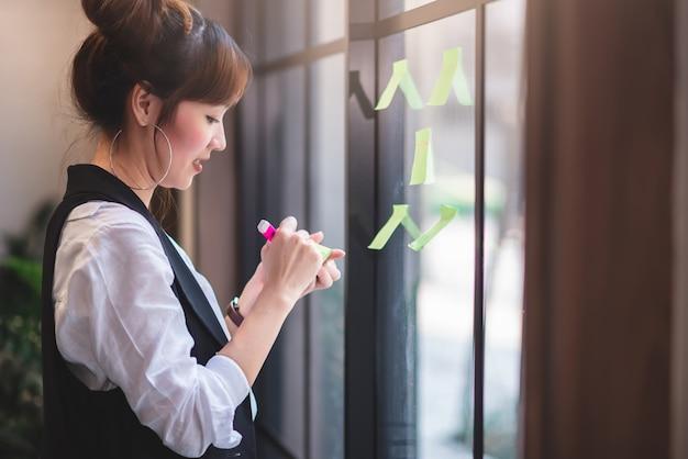 コワーキングスペースでチームと分析し、ブレーンストーミングするための付箋で書く創造的なビジネス人々