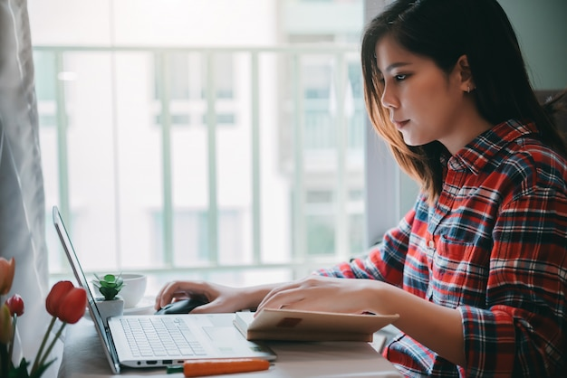 Красивая азиатская молодая женщина работая от дома на портативном компьютере пока сидящ на комнате кондо живущей с представлять уверенно