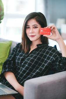 Азиатская молодая женщина держа кредитную карточку и используя портативный компьютер к ходить по магазинам онлайн дома живущей комнате. работайте дома и оставайтесь дома