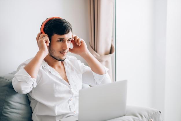 ラップトップコンピューターで作業して自宅で仕事をしながら音楽を聴くのにステレオヘッドセットを着ている白人の若いハンサムなビジネス男