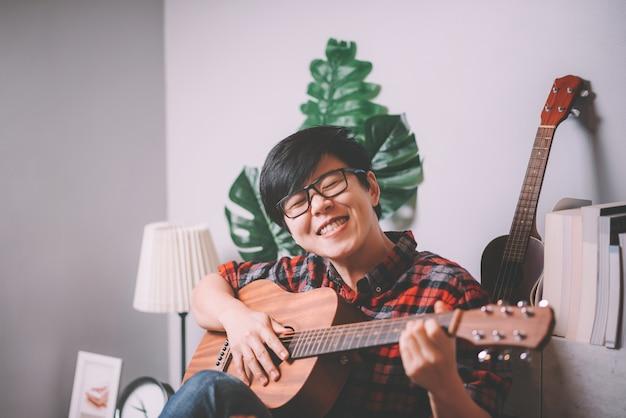 Молодой хипстер играет на гитаре дома для отдыха в гостиной дома