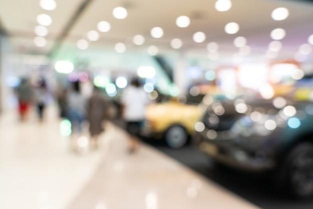 車と柔らかい稲妻のぼやけたディーラー店